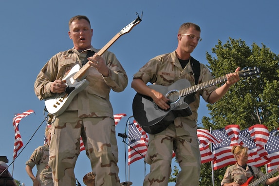 "OFFUTT AFB - Master Sgt Jimmy Weber and Senior Amn Clint Whitney take the crowd on a guitar ""ride"" during one of the band's ""Sundays on Parade"" concerts."