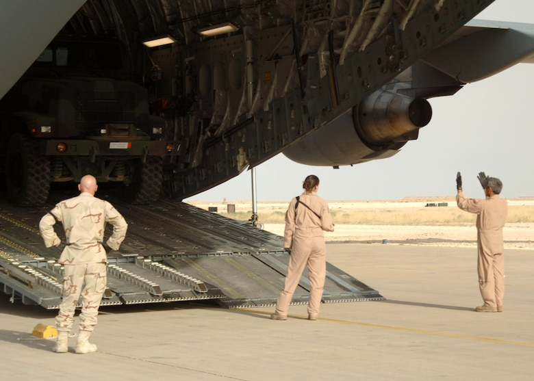 Airmen assigned to the 438th Aerial Port Flight and an aircrew from Charleston Air Force Base, S.C., coordinate the offload of a C-17 Globemaster III April 21 at Al Asad Air Base, Iraq. Since January, 438th APF Airmen have processed more than 32,000 passengers, 15,528 tons of cargo and more than 2,600 aircraft, keeping nearly 12,000 American servicemembers off the roads in convoys. (U.S. Air Force photo/Capt. Ken Hall)