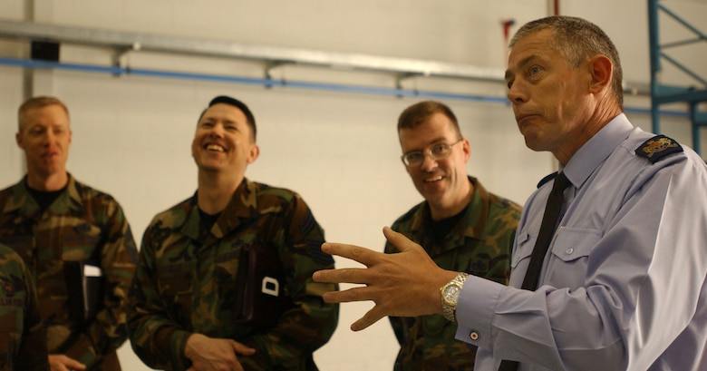 Warrant Officer Lindsey Morgan, right, from the British Royal Air Force talks to Airmen inside the 100th Maintenance Squadron hanger while (from left) RAF Mildenhall Command Chief Master Sgt. Michael Warner, Chief Master Sgt. Gregory Blue, and Senior Master Sgt. John Van Duser from the 100th MXS listen April 23, 2007. (U.S Air Force photo by Airman Brad Smith)