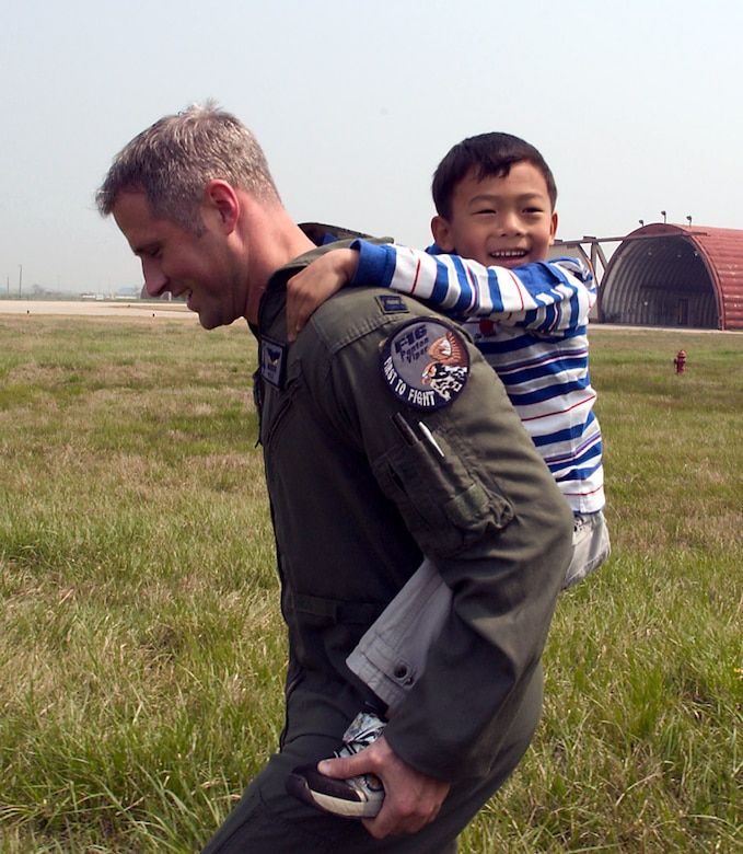 Capt. Tom Still gives a piggyback ride to a child from the Gunsan City orphanage April 27 at Kunsan Air Base, South Korea. Airmen from the 35th Fighter Squadron hosted the orphanage as part of the 8th Fighter Wing's Good Neighbor Program. The 35th FS is one of two F-16 Fighting Falcon squadrons assigned to the 8th Fighter Wing. Captain Still is a fighter pilot assigned to the 35th FS. (U.S. Air Force photo/Senior Airman Barry Loo)