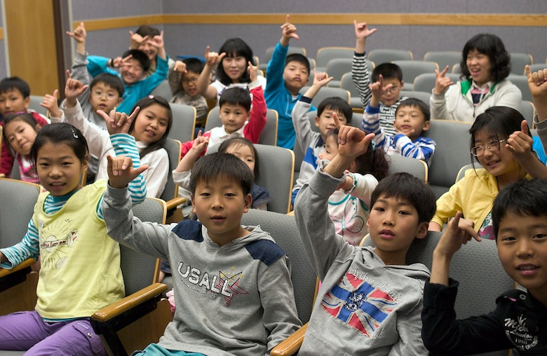 "Children from a Gunsan City orphanage ""push it up"" during their visit to the 35th Fighter Squadron April 27 at Kunsan Air Base, South Korea. The ""push it up"" hand gesture is a traditional way of recognizing other members of the squadron, to include the children who were honored guests during their visit. Squadron Airmen hosted the children as part of the 8th Fighter Wing's Good Neighbor Program commitment to supporting the local community. The 35th FS is one of two F-16 Fighting Falcon squadrons assigned to the 8th FW here. (U.S. Air Force photo/Senior Airman Barry Loo)"
