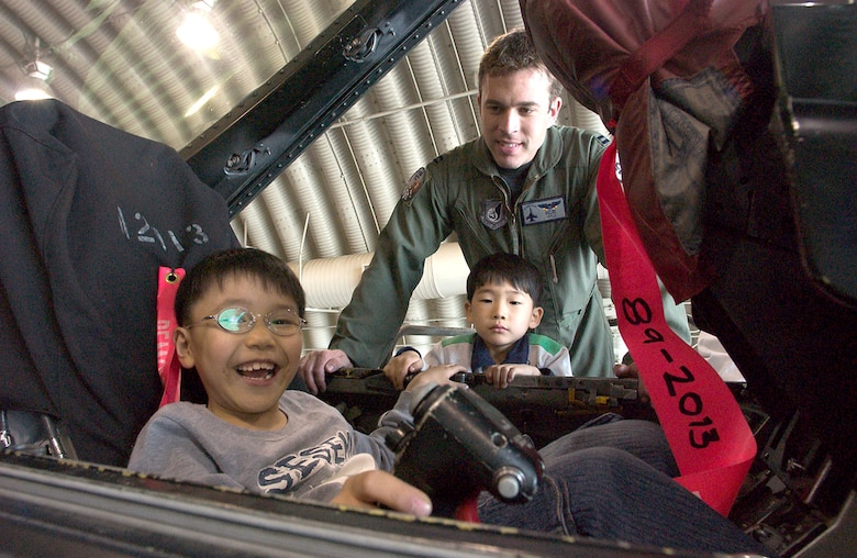 Capt. Aaron Jelinek shows an F-16 Fighting Falcon cockpit to children from a Gunsan City orphanage during their visit April 27 to Kunsan Air Base, South Korea. Airmen of the 35th Fighter Squadron hosted children from the orphanage as part of the 8th Fighter Wing's Good Neighbor Program. Captain Jelinek is a fighter pilot with the 35th FS. (U.S. Air Force photo/Senior Airman Barry Loo)