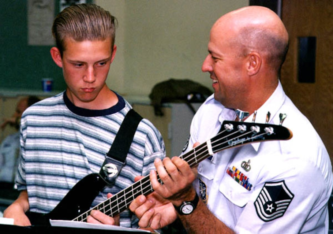 MSgt (ret) Scott Webring, from the USAF Academy Band, helps a bass student during a recent clinic with the Falconaires jazz band as part of the education outreach program.