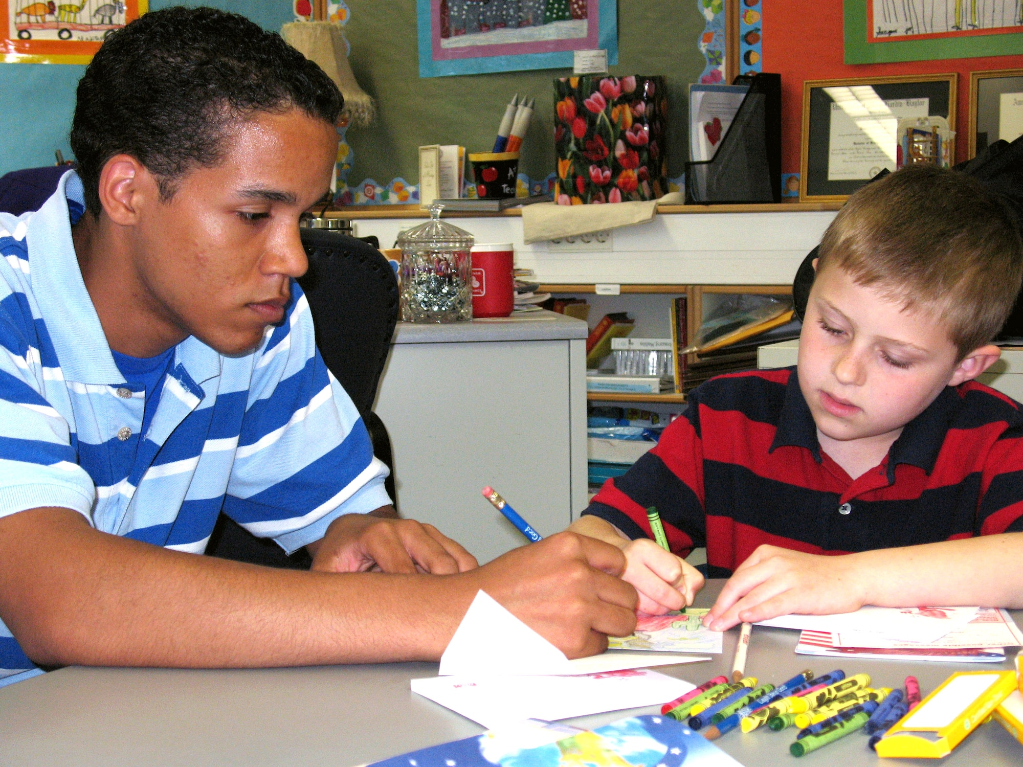 """Brice Relaford helps Caleb Parrish draw a card for his father April 26 at Ramstein Air Base, Germany. Brice and Caleb are """"Deployment Buddies,"""" which is a program for high school and elementary school students who have parents that have deployed or will deploy. The buddies pair up and spend a day doing activities such as making cards for their parents, dancing the """"Hokey Pokey"""" and playing games. The event happens once a month. Brice is a Ramstein High School junior. (U.S. Air Force photo/Staff Sgt. Leigh Bellinger)"""
