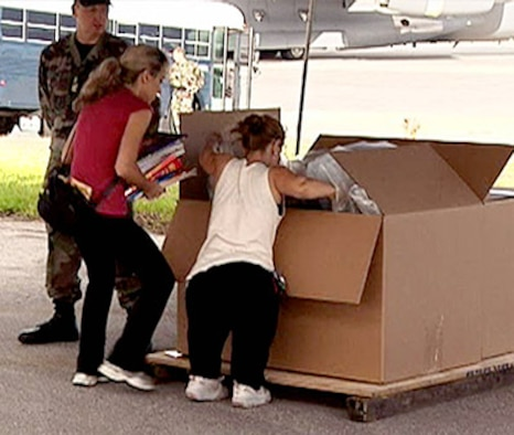First Lieutenant Robert O'Day stands guard as Amazing Race contestants Charla and Mirna take part in an Air Force humanitarian relief effort by filling a box with 500 pounds of essential supplies for locals on neighboring islands. Once their box reaches 500 pounds of supplies the cousins will board a massive C-17 cargo plane for an opportunity to experience an official Air Force airdrop exercise.