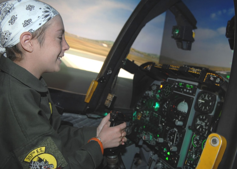 Kellie Miner-Durkit, 13, flies in an A-10 simulator at the 355th Operations Support Squadron. The simulator was one of several stops Miner-Durkit, a leukemia patient, made while visiting D-M April 27 as part of the Pilot for a Day program.