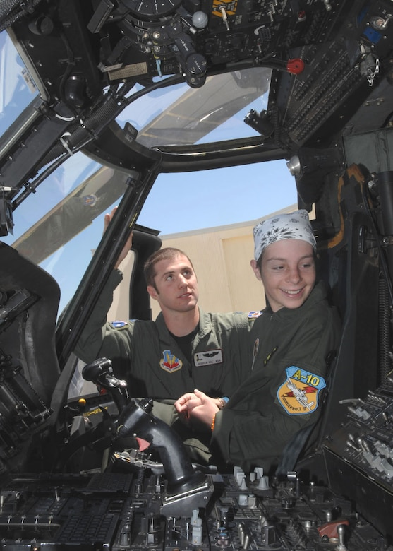 Thirteen-year-old Kellie Miner-Durkit sits in the pilot's seat of an HH-60 Pave Hawk helicopter, while Capt. Joshua Hallada, a pilot for the 55th Rescue Squadron here, explains the controls. The 55th RQS was one of several stops Miner-Durkit, a leukemia patient, made while visiting D-M April 27 as part of the Pilot for a Day program.