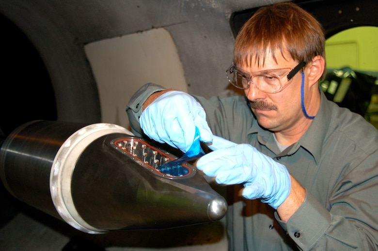 Ladd Henneman, a Lockheed Martin flight sciences engineer, removes a protective film from a Terminal High Altitude Area Defense missile forecone's infrared seeker window prior to an aerothermal test at Arnold Engineering Development Center's Hypervelocity Wind Tunnel 9 facility in Silver Spring, Md. The window is made from a new advanced material that will provide improved seeker performance at reduced cost. (Photo by Arnold Collier)