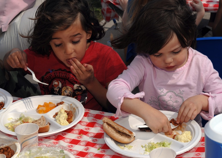 Noli Jones, 4, and her sister Dawn, 2, chow down on hamburgers and beans during the Child Development Center BBQ April 20. The BBQ is one of the many events that were held in April during the Month of the Military Child. (U.S. Air Force photo by Senior Airman Courtney Garrard)