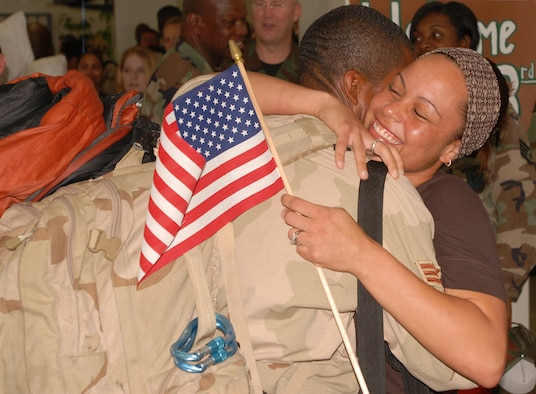 Senior Airman Perris Coleman of the 18th Equipment Maintenance Squadron at Kadena Air Base, Japan, embraces his wife after returning from a 120-day deployment to Kandahar, Afghanistan.  Airman Coleman was deployed with Kadena's  33rd Rescue Squadron. While in Afghanistan, the 33rd Rescue Squadron saved 116 lives and flew more than 200 sorties.  Dozens of Airmen from Kadena's 718th Aircraft Maintenance and the 18th EMS were also deployed with the 33rd RQS.  (U.S. Air Force photo by Airman 1st Class Ryan Ivacic)
