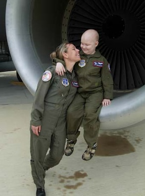 ANDREWS AIR FORCE BASE, Md. -- Capt. Susanne Schulz, 113th Airlift Wing Pilot for a Day (P4D) coordinator, exchanges smiles in the engine of a KC-135 Stratotanker with 8-year-old Sam Gates, who was diagnosed with leukemia last year. Members of the 459th Air Refueling Wing joined forces with the National Guard's 113th AW to host P4D. The program allows children with serious diseases to visit the wing and tour aircraft, the fire station, watch military working dogs and mingle with pilots and aircrew. The 459th ARW is a Reserve component of the U.S. Air Force. (U.S. Air Force photo by Staff Sgt. Amaani Lyle)