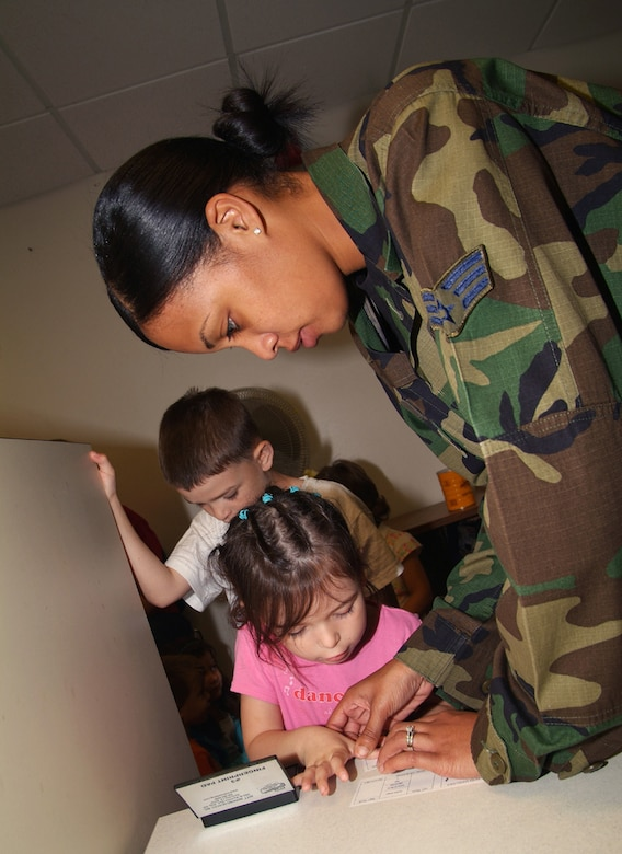 Richard Miller, 7, waits behind his sister, Adrianna, 4, as she is assisted putting thumbprints on her Operation Hero identification card by Senior Airman Roslyn Ball, 81st Training Support Squadron.  They are the children of Lt. Col. Richard and Yolany Miller, 334th Training Squadron commander.  (U.S. Air Force photo by Adam Bond)