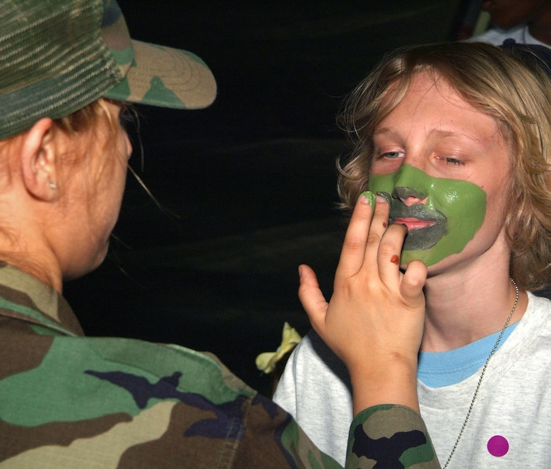 Airman Jounel Caceres, a chaplain's assistant, applies camouflage paint to the face of Dustin Vineyard, 13, at the deployment facility Saturday during Operation Hero.  Dustin's parents are Master Sgt. Chad andStaff Sgt.  Casie Vineyard, 81st Training Support Squadron and 403rd Wing, respectively.  (U.S. Air Force photo by Adam Bond)