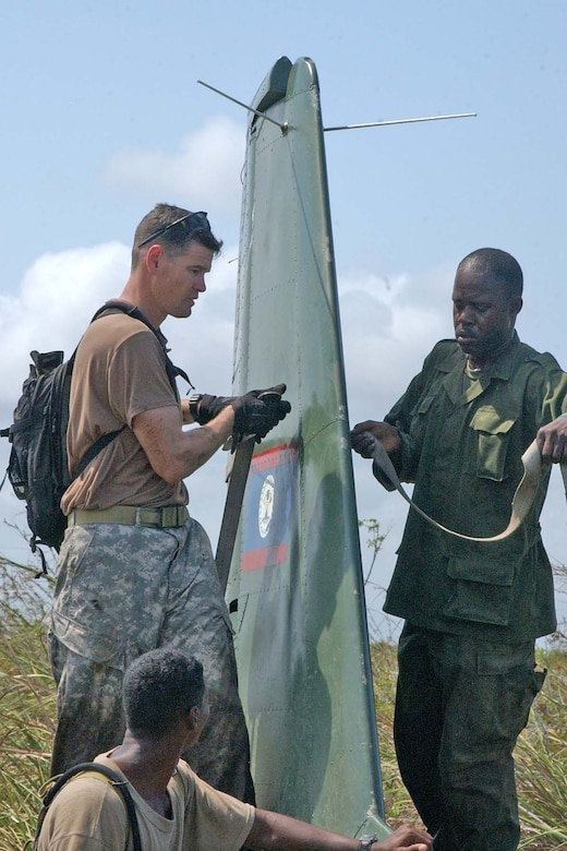 BELIZE CITY, BELIZE -- U.S. Army Sgt. 1st Class Mike Parks, 1st Battalion, 228th Aviation Regiment quality control noncommissioned officer in charge, and a soldier from the Belize Defence Force cargo strap the rudder of a downed BDF Defender aircraft. The downed BDF Defender aircraft was successfully slingloaded onto a U.S. Army UH-60 Black Hawk helicopter and delivered to the BDF air station at Belize City International Airport May 3. (U.S. Air Force photo by Staff Sgt. Chyenne A. Griffin)