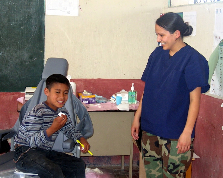Airman 1st Class Laura Valenzuela De La Hoya, a dental technician from Vandenberg AFB, Calif., shares a laugh with a Guatemalan child after his dental visit. Airman Valenzuela De La Hoya and Capt. (Dr.) Seth Briggs, also from Vandenberg, extracted 871 teeth and restored another 85 during the 10-day humanitarian mission to various regions of Guatemala in the last days of April. (U.S. Air Force Courtesy Photo)