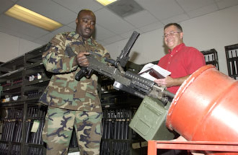 Vic Flores (right) observes as Master Sgt. Derrick Adkins, 452nd Security Forces armory noncommissioned officer in charge at March Air Reserve Base, demonstrates clearing procedures on one of the M240B machine guns in the inventory. (U.S. Air Force photo by Staff Sgt. Amy Abbott, 452 AMW/PA)