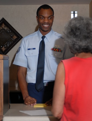 Staff Sgt. Richard Smith, 314th Service Squadron, helps guest Karen Metcalf check out of the Razorback Inn. The Razorback Inn won the 2006 AETC Excellence Award this past year. (USAF photo by A1C Steele Britton)
