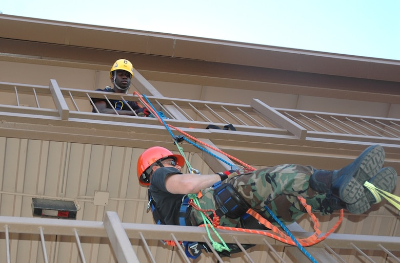 Staff Sgt. Daniel Rasmussen, a firefighter from D-M's fire protection flight, ascends a building using a life safety rope, while fellow firefighter Senior Airman Wilbert Carter guides from above. The rope rappelling was part of the high-angle operations portion of specialized rescue training taught at D-M April 16 through May 4 by three instructors from the United States Air Forces in Europe Fire Academy. (U.S. Air Force photo/Staff Sgt. Jake Richmond)