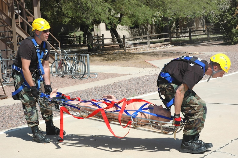 "Staff Sgt. Michael Long (left) and Airman 1st Class Jason Abbey, both firefighters at D-M, lower a dummy victim onto the ""helipad"" after a simulated canyon rescue here April 30. The specialized rescue training was part of a three-week course taught by three instructors from the United States Air Forces in Europe Fire Academy, who traveled here and certified 19 D-M firefighters. (U.S. Air Force photo/Staff Sgt. Jake Richmond)"