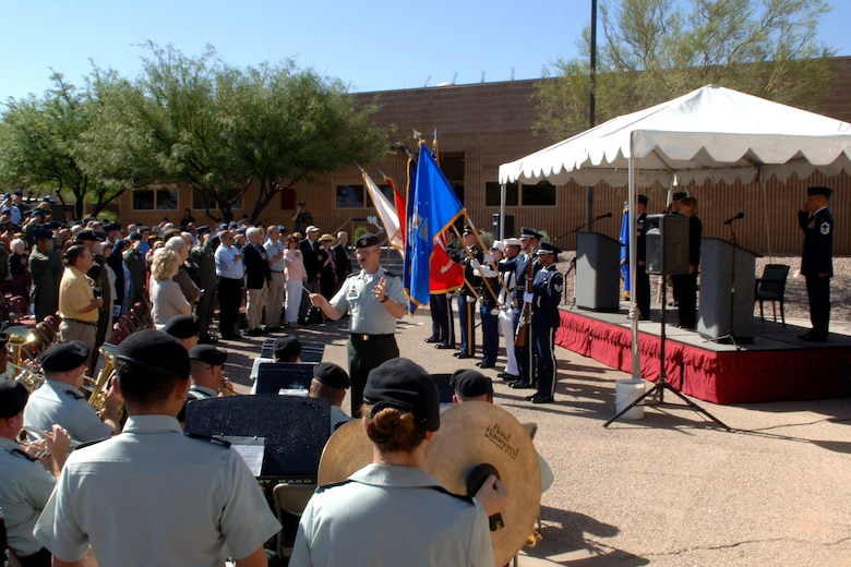 More than 200 military and civilians salute the U.S. flag as the national anthem is played by the 36th Army Band, May 9, during a ribbon cutting ceremony held for the unveiling of the new James H. Doolittle Combined Air and Space Operations Center at Davis-Monthan Air Force. The building was named in honor of General James H. Doolittle, 12th Air Force's first commander and the Doolittle Raiders for their heroic actions during World War II.  Photo by Tech. Sgt. Kerry Jackson