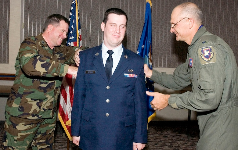 Col. Bryan Gallagher (left), 95th Air Base Wing commander, and Col. Arnie Bunch, 412th Test Wing commander, tack stripes on to Staff Sgt. Thomas Gilchrist during the Team Edwards Promotion ceremony at the Conference Center here April 30. (Photo by Chad Bellay)