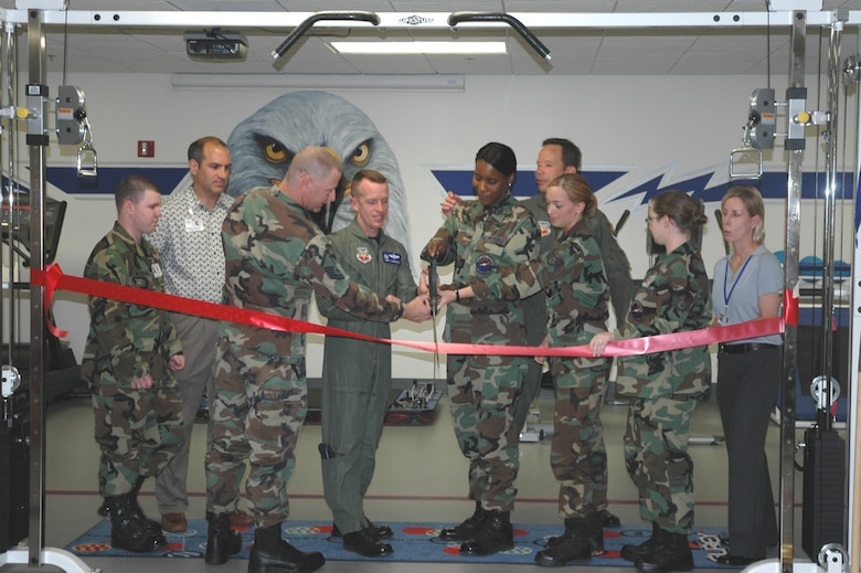 Col. Kent Laughbaum, commander of the 355th Fighter Wing, joins the 355th Medical Operations Squadron's Physical Therapy Team to cut the ribbon for the grand opening of the new Physical Therapy Clinic here April 26. The clinic is expected to treat about 600 patients per month. (U.S. Air Force photo/Airman Jamie Coggan)