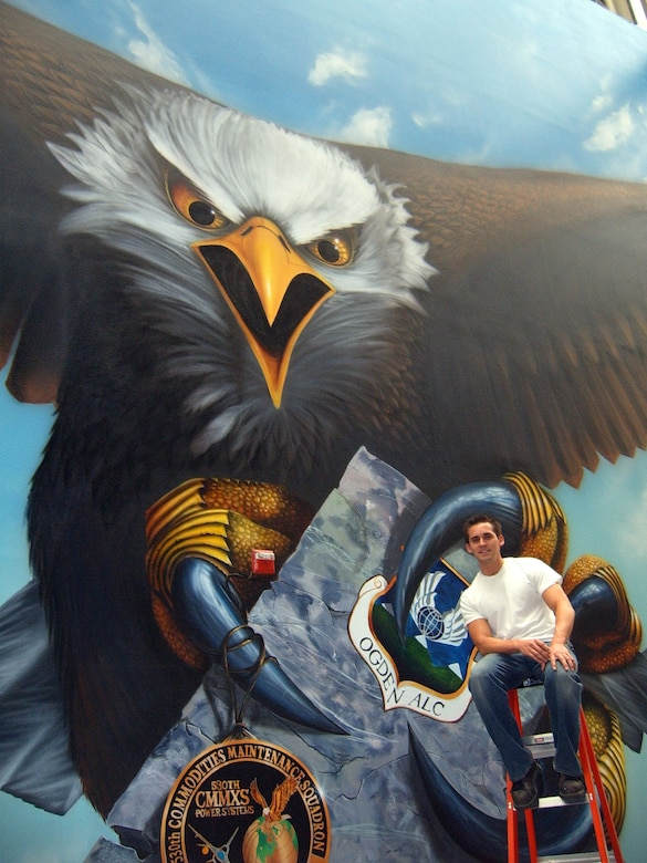 """Jasey Colunga, machinist with the 530th Commodities Maintenance Squadron, leans on his most recently completed artwork at Hill Air Force Base. This is the single largest work of art Mr. Colunga has completed. The entire mural spans 170 feet by 35 feet, and is too wide to capture in a single photo. Drafts for the mural began with roadmaps from Texas to Utah representing the connection the unit has had with Texas in the past. Those drafts were tossed aside, however, and replaced with an all encompassing picture of Utah. The mural depicts southern Utah on the left and northern Utah on the right side. """"The mural is really just to boost morale in our building,"""" said Mr. Colunga. """"It turns our industrial workplace into an interesting shop that people remember."""" Courtesy Photo"""