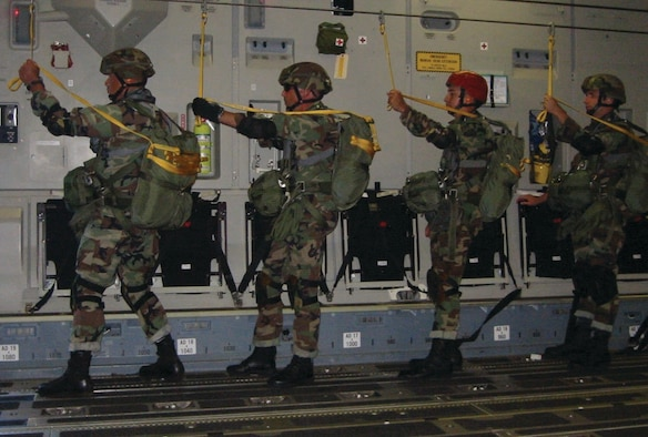 Four 36th Contingency Response Group Airman stand ready to parachute from a C-17.
