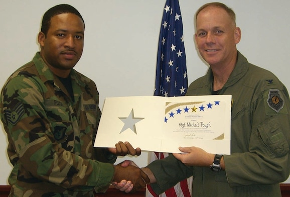 Col. Joel Westa congratulates Staff Sgt. Michael Pough for his contributions to the tax center.  Sergeant Pough was the top tax preparation volunteer for the year.
