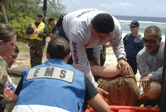 Mark Terlage, secures the victim's neck, as a joint rescue team moves the victim onto a backboard.  The Air Force, Army, Navy and Coast Guard performed a joint resuce April 26.