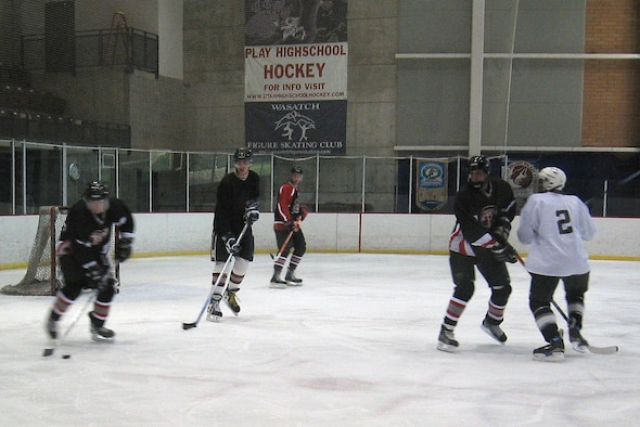 Members of the Hill Air Force Base ice hockey team (dark jerseys) attempt to clear the puck from their defensive zone during Sunday's game at the Weber County Ice Sheet, Ogden, Utah. The Hill AFB team competes in a community league against other teams with varying talent levels. The talent level of the competition on Sunday was extremely high as the Hill AFB team lost the game 4-12. The team is waiting to find out when its first playoff game will be held. As of press time for the Hilltop Times, the team expects to play Sunday, but the time is uncertain. Keep reading the Hilltop Times for ice hockey coverage as Hill AFB makes a run in the playoffs. (Photo by Margarita Smith)
