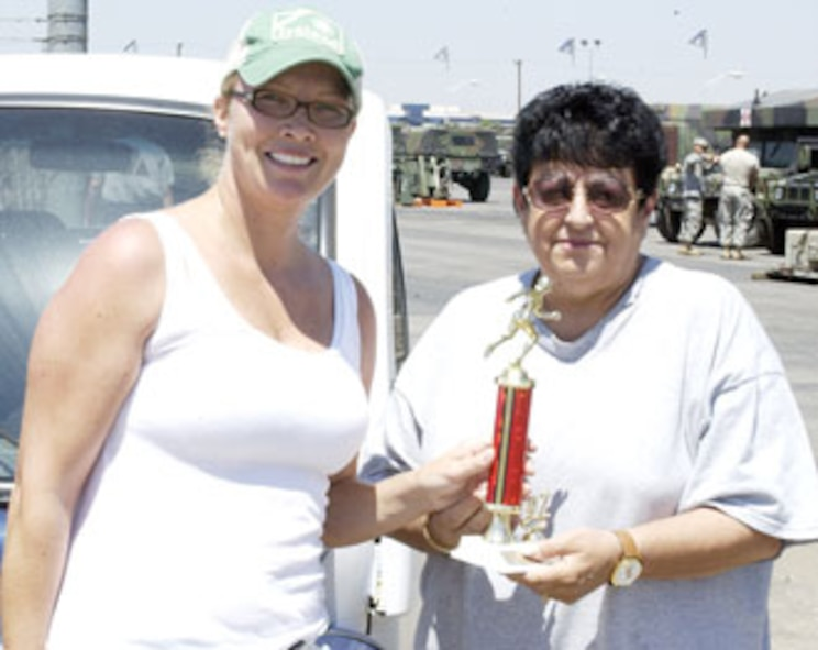 Brenda Hendricksen receives her first place trophy from Sports and Fitness director