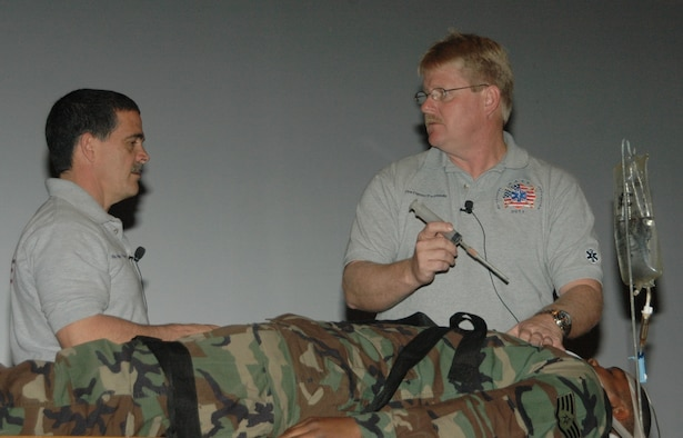Florida firefighters Ronny Garcia (picture left) and Kevin Reed demonstrate medical techniques on Staff Sgt. Talmage Williams, 28th Munitions Squadron munitions storage crew chief, during a SAFE brief April 27 at the base theater.  SAFE features members of the medical and law enforcement  community who share their no-hold barred and grittily honest experiences with audiences around the world. (U.S. Air Force photo/Tech. Sgt. Todd Wivell)