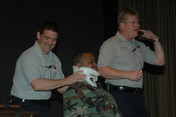 Florida firefighters Ronny Garcia (pictured left) and Kevin Reed demonstrate medical techniques on Staff Sgt. Talmage Williams, 28th Munitions Squadron munitions storage crew chief, during a SAFE brief April 27 at the base theater.  SAFE features members of the medical and law enforcement  community who share their no-hold barred and grittily honest experiences with audiences around the world. (U.S. Air Force photo/Tech. Sgt. Todd Wivell)
