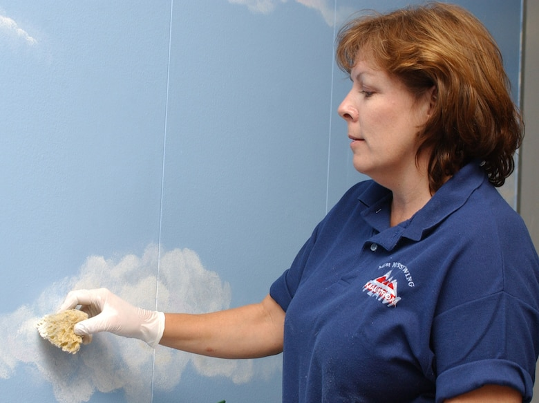Karen Ray  sponge paints a cloud on a wall outside the command section of Garrard Hall.  She's the spouse of Lt. Col. Stephen Ray, 81st Training Group deputy commander.  (U.S. Air Force photo by Kemberly Groue)