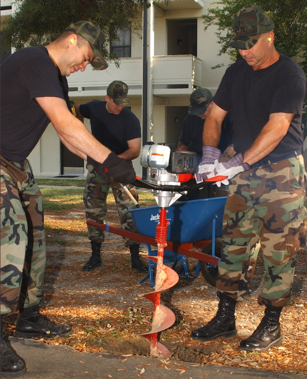 Staff Sgt. Jesus Gutierrez, left foreground, and Master Sgt. Brad Belford drill a hole for the installation of a grill in the courtyard of permanent party dormitories 4813 and 4815.  In the background, Master Sgt. Gunny McCune, left, and Staff Sgt. Bryan Carnwell mix concrete for the grill post.   All four men are assigned to the 81st Civil Engineer Squadron.  (U.S. Air Force photo by Kemberly Groue)