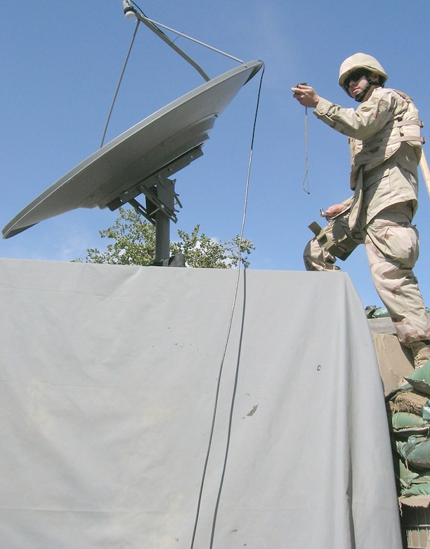 Sergeant Davis uses a compass to make sure the azimuth of the AFN satellite dish is correct at an outpost in eastern Afghanistan.  (Courtesy photo)