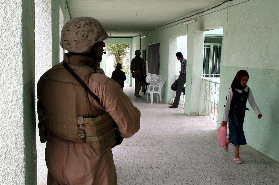 A Marine keeps a watchful eye on the perimeter of a school while an Iraqi girl walks to her class in the city of Fallujah on May 16. Marines in 2nd Platoon of Company E, 2nd Battalion, 6th Marine Regiment, Regimental Combat Team 6, worked side-by-side with the Iraqi Police in the city of Fallujah to distribute soccer balls and numerous other supplies to students at two schools.