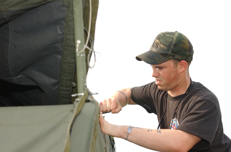 Staff Sgt. Richard Durling, 81st Civil Engineer Squadron tightens the end of a tent May 15.  The 81st CES and the 81st SVS assembled 10 Temper tents for next week's exercise.  (U.S. Air Force photo by Kemberly Groue)