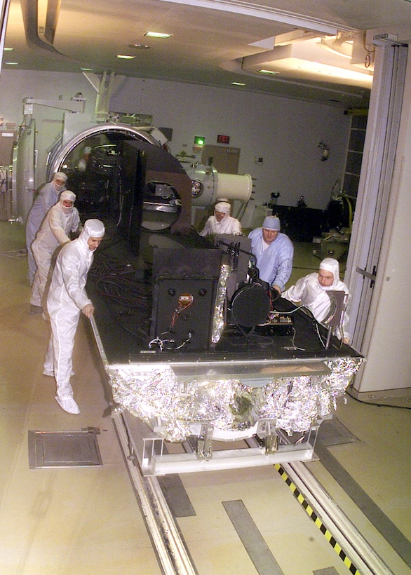From left to right, David Stanek, instrument technician; Roger Johnson, instrument technician; Josh Drumm, systems test engineer; Ed White, senior systems test engineer; Ricky Bush, outside machinist; and Aaron Wojcik, systems test engineer, at the Arnold Engineering Development Center's 7V Space Chamber, remove an optical bench in the clean room at the seven by 21-foot test chamber. The bench's removal is part of a major upgrade project that began with the chamber's demolition by Western Environmental, Inc. The changes will not significantly affect the size of the facility. Some of the improvements to the chamber will include changing the airflow from horizontal to vertical and changing the chamber to a class 1,000 (number of particles per million) clean room.