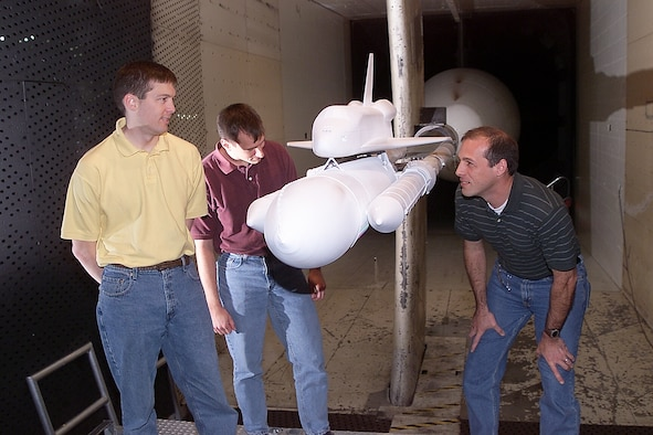 Jim Greathouse, CFD analyst, left to right, Darby Vicker, CFD analyst, and Bob Ess, program manager, all from NASA Johnson Space Center, examine the shuttle model during a model change at AEDC's 16-foot transonic wind tunnel.