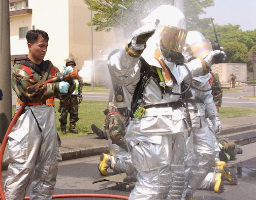 Senior Airman Jorley Vivo, 374 CES, hoses down fellow firefighters after a simulated contamination scenario during the exercise. (Photo by Airman Leandra Hernandez VIRIN 070508-F-8186H-043)