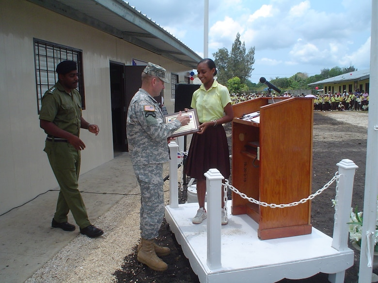 Brig. Gen. Ken Keen receives a thank-you plaque from a girl who will attend the newly constructed school in Hattiesville, Belize, May 18.  This two-room school is one of four schools built by U.S. and Belizean Defense Forces personnel.  U.S. Air Force photo by Capt. Alysia Harvey