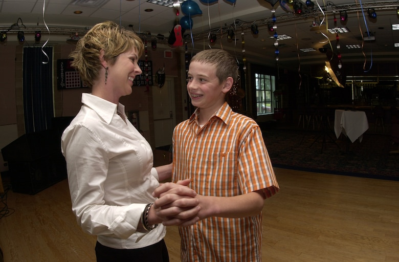 Jan Menard and her 12-year-old son Zachary Fair exchange smiles as they enjoy dancing to some slow country music during the Annual Mother/Son Dance held May 10 at the Goodfellow Events Center. (U.S. Air Force photo by Airman 1st Class Luis Loza Gutierrez)