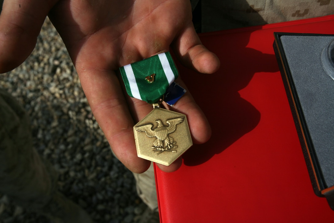 Lance Cpl. Blake A Soileau, 19, from Zachary, La., holds his Navy and Marine Corps Commendation Medal, with combat distinguishing device that he was awarded in a ceremony here, May 21. He received the award for exposing himself to enemy machine gun fire while stopping a explosive-laden dump truck from entering the platoon's forward operating base. His accurate fire brought the truck to a halt saving the lives of his fellow Marines. (Photo by Lance Cpl. Christopher Zahn)