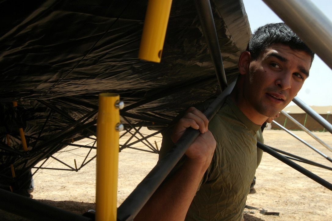 Lance Cpl. Alexander Garcia, from the 26th Marine Expeditionary Unit's Command Element, helps the unit's Headquarters Commandant Section erect a tent at a MEU camp in the Middle East May 22, 2007.  The section is responsible for attending to virtually every day to day need of MEU living spaces ashore and at sea.  (Offical USMC photo by Cpl. Jeremy Ross) (Released)