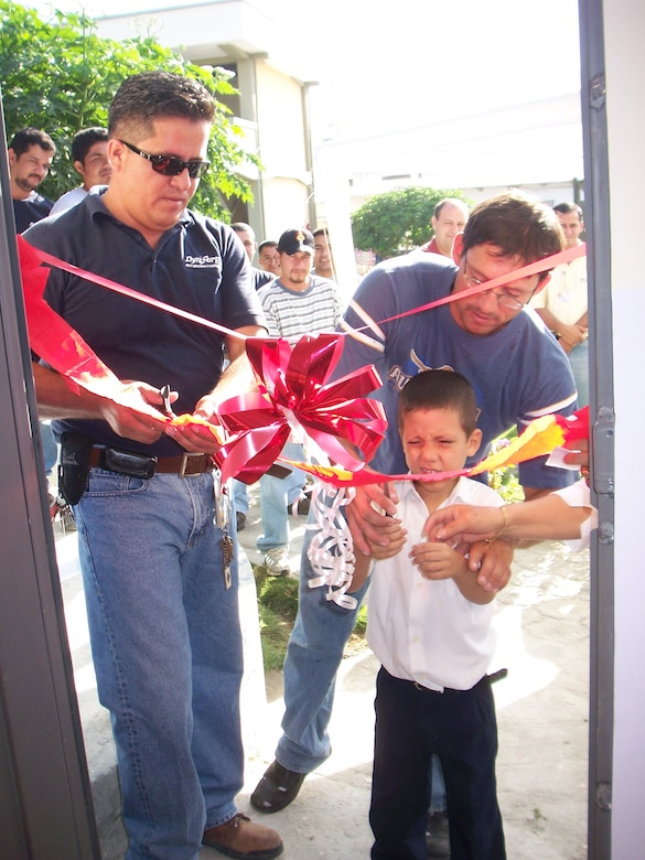 Volunteers from the 478th Expeditionary Operations Squadron cut the ribbon on a renovated classroom at a local school for the handicapped along with one of the visually impaired students who will be attending classes there. (Photo by Maj. Chris Hemrick)