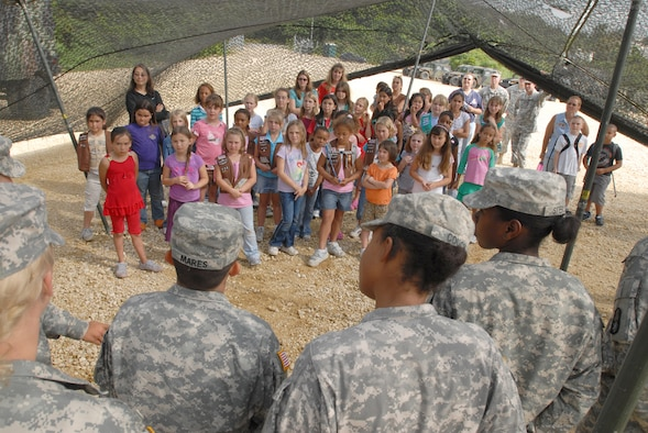 Girl Scout Troops 414, 432, 433, and 435 are introduced to women from the 1-1 Air Defense Artillery Battalion at Kadena Air Base, Japan, May 15. The women in turn showed the girls the different pieces of artillery equipment each one works on. The purpose of the visit was to show the girls the importance of the unit in protecting them against any danger from our enemies, and to show that there are plenty of good women role models in the services they can look up to.