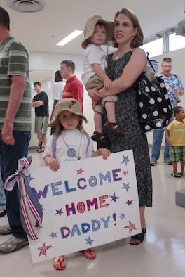 Laura Rice, with her two children Emily and Jonathan, wait for the arrival of her husband Maj. Jon Rice, 18th Operations Support Squadron, from his four-month deployment to Balad Air Base, Iraq, May 19. More than 120 members returned to Kadena Air Base, Japan, from deployment that day.