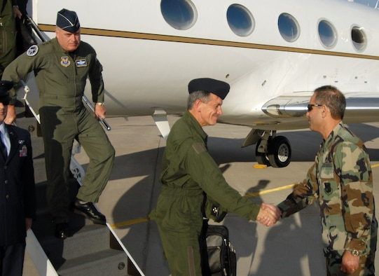 French Lt. Gen. Jean-Paul Palomeros, vice chief of staff of the French air force, shakes hands with Col. Mohsen Parhizkar, 377th Air Base Wing vice commander, upon the general?s arrival here. During his May 9-10 visit, the general toured the 58th Special Operations Wing with Lt. Gen. Howie Chandler, deputy chief of staff for Operations, Plans and Requirements, Headquarters U.S. Air Force, Washington, D.C., who is stepping off the plane.  U.S. Air Force photo by Laurence Zankowski